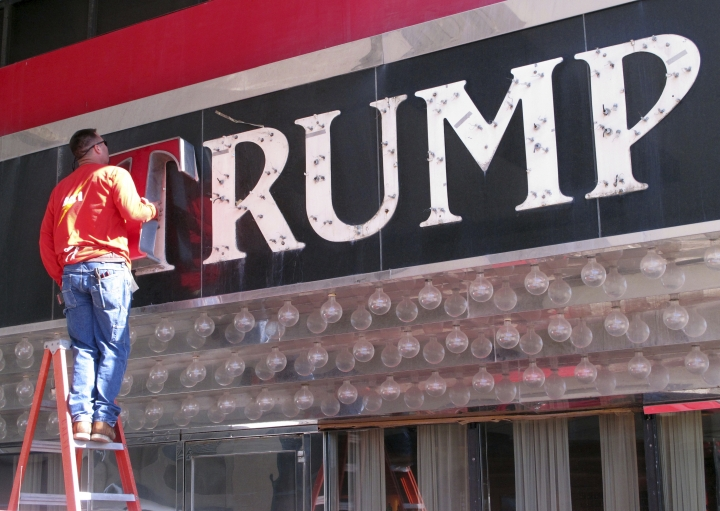 FILE - In this file photo taken Oct. 6, 2014, a worker removes letters from a Trump logo in Atlantic City, N.J.China has granted preliminary approval for 38 new Trump trademarks, fueling concerns about conflicts of interest and preferential treatment of the U.S. president. The marks pave the way for branded spas, golf clubs, hotels, and even private body guard and escort services in China _though it's not clear if those businesses will actually materialize. (AP Photo/Wayne Parry, File)