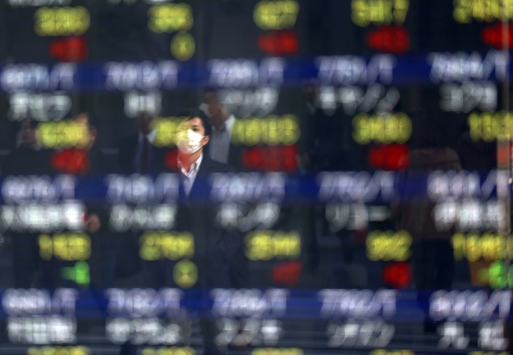 A man is reflected on an electronic stock board of a securities firm in Tokyo, Thursday, March 9, 2017. Asian stock markets were mostly lower Thursday after news of a big buildup in U.S. oil stockpiles depressed crude prices and shares of energy companies. (AP Photo/Eugene Hoshiko)