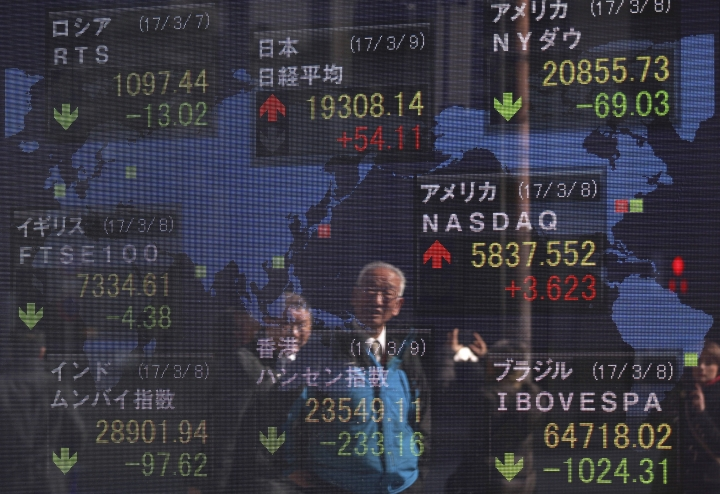 Pedestrian are reflected on an electronic stock board of a securities firm in Tokyo, Thursday, March 9, 2017. Asian stock markets were mostly lower Thursday after news of a big buildup in U.S. oil stockpiles depressed crude prices and shares of energy companies. (AP Photo/Eugene Hoshiko)