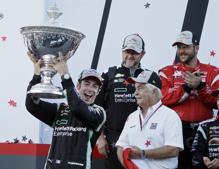 FILE - In this Sept. 18, 2016, file photo, Simon Pagenaud, of France, holds up the Astor Cup after winning the IndyCar auto race and IndyCar championship as team owner Roger Penske, lower right, looks on in Sonoma, Calif. Pagenaud leads a dominant Team Penske squad into IndyCar's season-opening race on Sunday, and the Frenchman has his eye on a second consecutive series championship. (AP Photo/Eric Risberg, File)