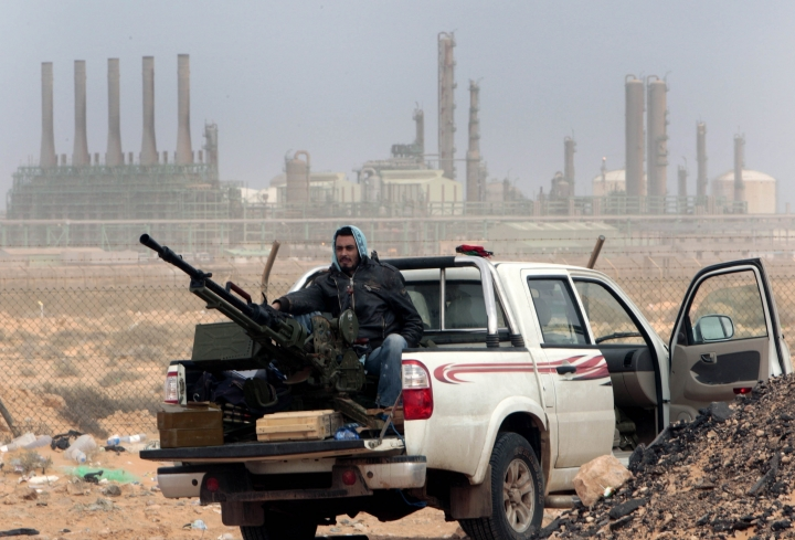 FILE - In this March 5, 2011 file photo, an anti-government rebel sits with an anti-aircraft weapon in front an oil refinery in Ras Lanouf, eastern Libya. The fight for Libya's Ras Lanuf refinery and nearby Sidr depot threatens to spiral into open conflict between rival factions vying for power from east and west. With both sides claiming the facilities as their own but control unclear, decisive days lie ahead. (AP Photo/Hussein Malla, File)