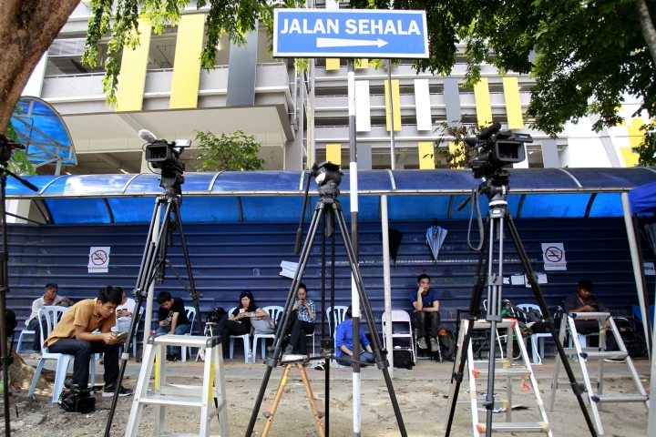 """Journalists wait outside forensic department at Kuala Lumpur Hospital in Kuala Lumpur, Malaysia on Sunday, March 12, 2017. Malaysia's Foreign Minister Anifah Aman said the government hopes to begin formal talks with North Korea in the """"next few days"""" on solving a diplomatic dispute that has seen the two countries bar each other's citizens from leaving. The dispute stems from the mysterious poisoning death of the estranged half brother of North Korean leader Kim Jong Un on Feb. 13 at Kuala Lumpur's airport.(AP Photo/Daniel Chan)"""