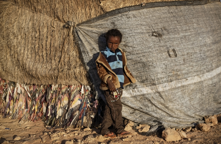 In this photo taken Thursday, March 9, 2017, a boy who fled the drought stands next to the makeshift hut where he sleeps in a camp for the displaced in Qardho in Somalia's semiautonomous northeastern state of Puntland. Somalia has declared the drought a national disaster, part of what the United Nations calls the largest humanitarian crisis since the world body was founded in 1945, and with animals being central to many the drought threatens their main sources of nutrition and survival. (AP Photo/Ben Curtis)