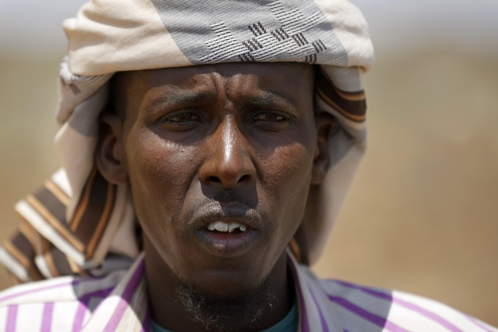 In this photo taken Wednesday, March 8, 2017, herder Ahmed Haji, 30, recounts how he trekked thousands of kilometers with his herd in search of greener pasture in a remote desert area near Bandar Beyla in Somalia's semiautonomous northeastern state of Puntland. Somalia has declared the drought a national disaster, part of what the United Nations calls the largest humanitarian crisis since the world body was founded in 1945, and with animals being central to many the drought threatens their main sources of nutrition and survival. (AP Photo/Ben Curtis)