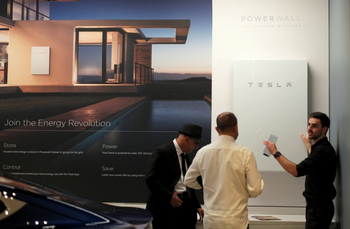 A Tesla representative (R) demonstrates the Tesla Powerwall battery storage device to potential customers at the Tesla store in Sydney, Australia, March 13, 2017.    REUTERS/Jason Reed