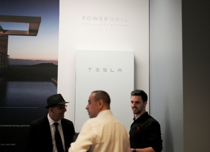 A Tesla representative (R) chats with potential customers alongside a Tesla Powerwall battery storage device at the Tesla store in Sydney, Australia, March 13, 2017.   REUTERS/Jason Reed
