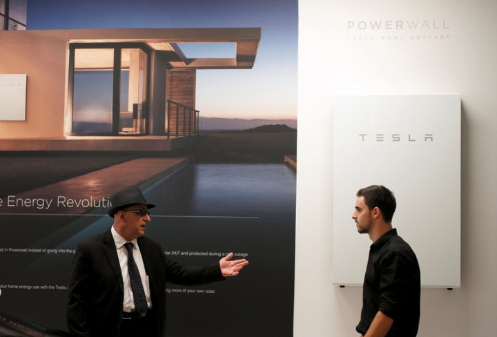 A Tesla representative (R) stands alongside a Tesla Powerwall battery storage device as he talks with a potential customer at the Tesla store in Sydney, Australia, March 13, 2017.  REUTERS/Jason Reed