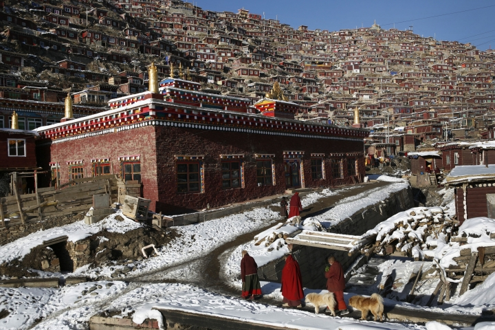 FILE - In this Nov. 23, 2009, file photo, Tibetan nuns walk near houses and monastery built on the mountain also known as Sertar Buddhist Institution or Larung Gar in Sertar county, southwest China's Sichuan province. China says it is rebuilding the major center of Buddhist learning in the country's west, following reports last year that the complex was being demolished and its residents evicted. An official and state media on Tuesday, March 14, 2017 said the project aims to eliminate dangers to safety and health at Larung Gar, which had been home to thousands of monks, nuns and laypeople studying the religion. (Chinatopix via AP, File)
