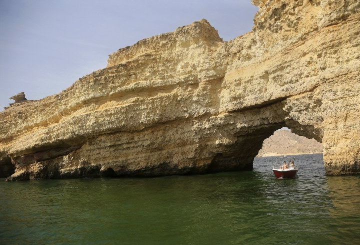 In this Feb. 26, 2017 photo, a boat drifts under a coastal arch into a green algae mass in the Gulf of Oman. Scientists who study the algae say the microscopic organisms are thriving in new conditions brought about by climate change, and displacing the zooplankton that underpin the local food chain, threatening the entire marine ecosystem. (AP Photo/Sam McNeil)