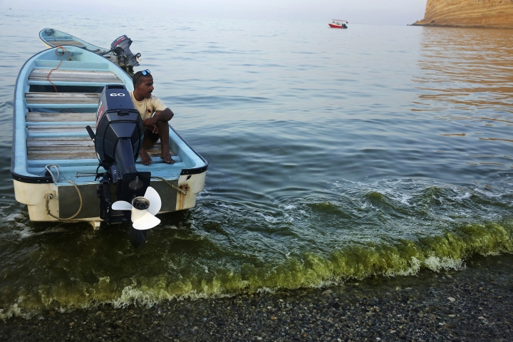 In this Mar. 3, 2017 photo, a wave colored with dark green algae washes on the beach of Bandar al-Jissah, Oman underneath Bassem al-Husn, 24. Scientists who study the algae say the microscopic organisms are thriving in new conditions brought about by climate change, and displacing the zooplankton that underpin the local food chain, threatening the entire marine ecosystem. (AP Photo/Sam McNeil)