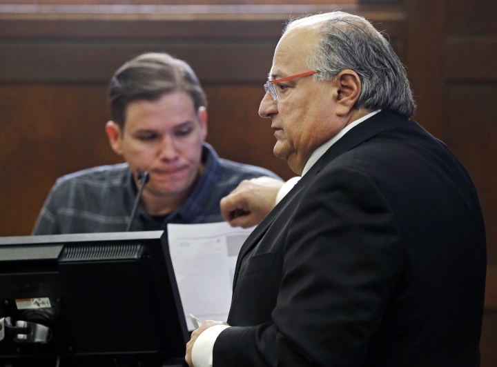 George Leontire, right, defense attorney for defendant Aaron Hernandez, shows paperwork to tattoo artist David Nelson who testifies during Hernandez' double murder trial in Suffolk Superior Court, Wednesday, March 15, 2017, in Boston. Hernandez is on trial for the July 2012 killings of Daniel de Abreu and Safiro Furtado who he encountered in a Boston nightclub. The former New England Patriots NFL football player is already serving a life sentence in the 2013 killing of semi-professional football player Odin Lloyd. (AP Photo/Elise Amendola, Pool)