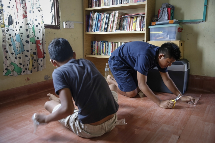 In this March 11, 2017, photo, Christian Burmese refugees fix the linoleum floor of their classroom in Kuala Lumpur, Malaysia. An Associated Press analysis suggests that the people hurt most by President Donald Trump's planned deep cuts in refugee visas are from not any of the six Muslim countries listed in his travel ban, but Myanmar. (AP Photo/Joshua Paul)