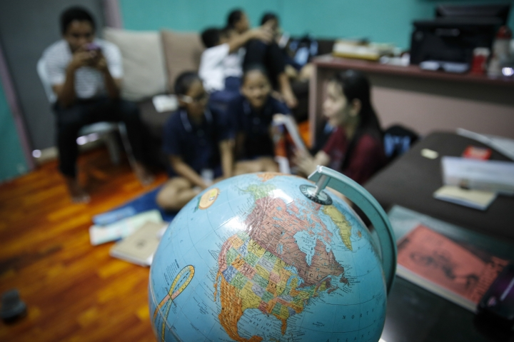 In this March 11, 2017, photo, Christian Burmese refugees sit in a classroom in Kuala Lumpur, Malaysia. An Associated Press analysis suggests that the people hurt most by President Donald Trump's planned deep cuts in refugee visas are from not any of the six Muslim countries listed in his travel ban, but Myanmar. (AP Photo/Joshua Paul)