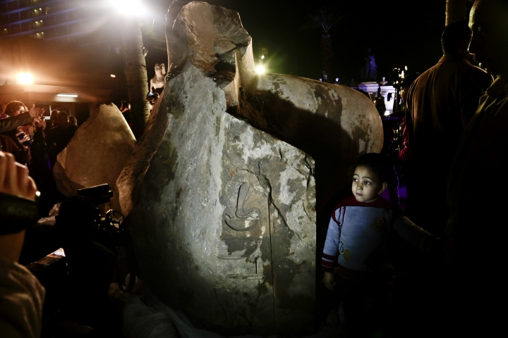 A boy looks at a stone, part of a statue of King Psamtek 1, after a press conference at the Egyptian museum in Cairo, Thursday, March 16, 2017. The three-ton torso of the massive statue was lifted on Monday from mud and groundwater where it was recently discovered in a Cairo slum. (AP Photo/Nariman El-Mofty)