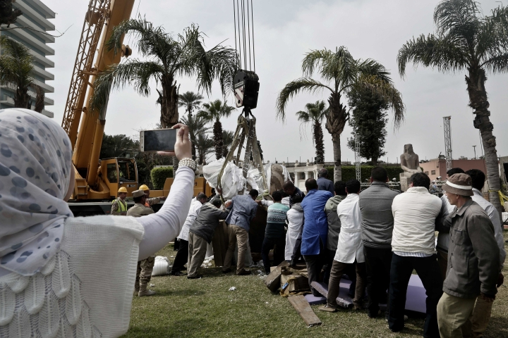 Antiquities workers bring down stone parts of the statue of King Psamtek l at the Egyptian museum in Cairo, Thursday, March 16, 2017. Egypt's antiquities minister Khaled el-Anani, told at a news conference that the colossus discovered last week in an eastern Cairo suburb almost certainly depicts Psamtek I, who ruled Egypt between 664 and 610 B.C. (AP Photo/Nariman El-Mofty)