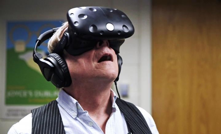 "In this Jan. 26, 2017, photo, Joseph Nugent, a Boston College English professor, wears virtual reality goggles at the school's virtual reality lab in Boston. College students in Boston are developing a virtual reality game based on James Joyce's ponderous tome ""Ulysses."" Nugent says the goal of ""Joycestick"" is to expose new audiences to the works of one of Ireland's most celebrated authors and to give a glimpse of how virtual reality can be used to enhance literature. (AP Photo/Charles Krupa)"