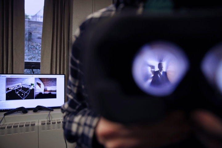 """In this Jan. 26, 2017, photo, Boston College student Michael Quinn holds up virtual reality goggles at a virtual reality lab at Boston College in Boston. College students in Boston are developing a virtual reality game based on James Joyce's ponderous tome """"Ulysses."""" (AP Photo/Charles Krupa)"""