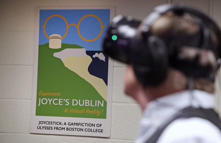 """In this Jan. 26, 2017, photo, Joseph Nugent, a professor of English at Boston College, wears virtual reality goggles at the school's virtual reality lab in Boston. College students in Boston are developing a virtual reality game based on James Joyce's ponderous tome """"Ulysses."""" Nugent says the goal of """"Joycestick"""" is to expose new audiences to the works of one of Ireland's most celebrated authors and to give a glimpse of how virtual reality can be used to enhance literature. (AP Photo/Charles Krupa)"""