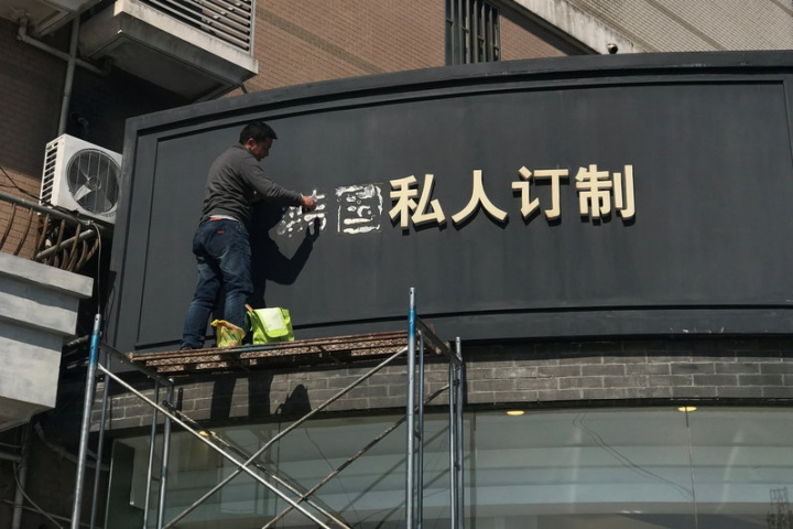 A worker removes part of a sign that consists of the Chinese characters that collectively read South Korea, at a shop in Shanghai, China March 15, 2017. REUTERS/Aly Song