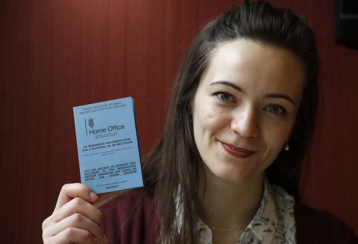 """In this Wednesday, March 8, 2017 photo, Dora-Olivia Vicol from Romania shows her UK Residence Documentation during and interview with Associated Press in London, Wednesday, March 8, 2017. Oxford University PhD student Vicol said she spent weeks trying to get a document from her homeland, Romania, to prove she had health coverage. """"I felt like I was going to fall through the cracks,"""" she said. (AP Photo/Frank Augstein)"""