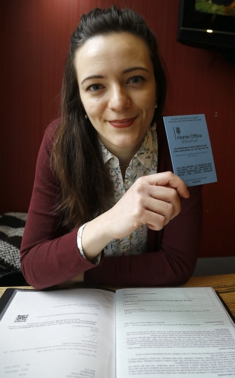 "In this Wednesday, March 8, 2017 photo, Dora-Olivia Vicol from Romania shows her UK Residence Documentation during and interview with Associated Press in London, Wednesday, March 8, 2017. Oxford University PhD student Vicol said she spent weeks trying to get a document from her homeland, Romania, to prove she had health coverage. ""I felt like I was going to fall through the cracks,"" she said. (AP Photo/Frank Augstein)"
