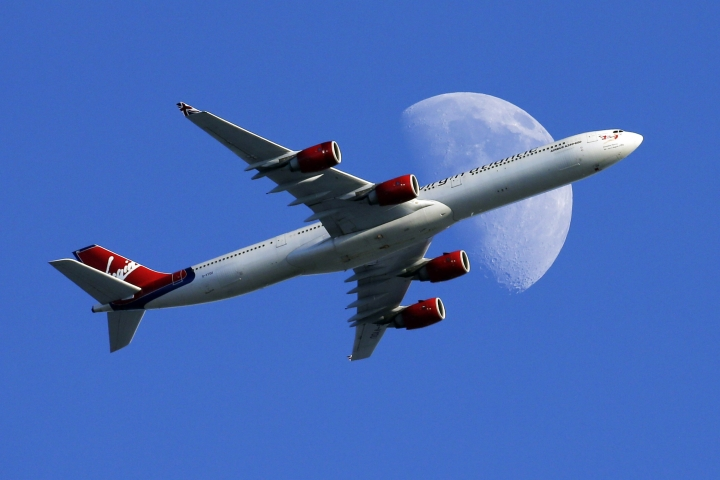 FILE - In this Sunday, Aug. 23, 2015, file photo, a Virgin Atlantic passenger plane crosses a waxing gibbous moon on its way to the Los Angeles International Airport, in Whittier, Calif. Alaska said Wednesday, March 22, 2017, that it will retire the Virgin brand, probably in 2019. Alaska announced in 2016, that it was buying Virgin, but CEO Brad Tilden held out hope to Virgin fans that he might keep the Virgin America brand, and run it and Alaska as separate airlines under the same corporate umbrella. (AP Photo/Nick Ut, File)