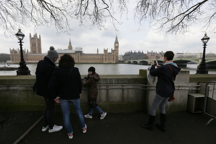 Tourists view parliament from across the River Thames, with Westminster Bridge, right, in London, Thursday March 23, 2017, the scene of an attack. On Wednesday a knife-wielding man went on a deadly rampage, first driving a car into pedestrians then stabbing a police officer to death before being fatally shot by police within Parliament's grounds in London. (AP Photo/Tim Ireland)