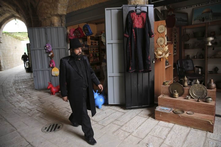 """In this Wednesday, March 22, 2017 photo, a Palestinian actor dressed as ultra Orthodox Jew walks during a shoot of the """"Heaven's Gate"""" movie in a recreated alleyway of Jerusalem's Old City in Khan Younis, Gaza Strip. Surrounded by militant training sites on uprooted Jewish settlement lands, the first movie set in the Gaza Strip is growing, depicting the history-rich, volatile alleyways of Jerusalem's Old City. (AP Photo/Adel Hana)"""