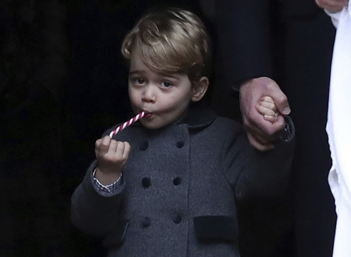 FILE - In this Sunday, Dec. 25, 2016 file photo, Prince George eats a sweet as he leaves following the morning Christmas Day service at St Mark's Church in Englefield, England. Kensington Palace says Prince George will attend the Thomas's Battersea prep school beginning in September. The Duke and Duchess of Cambridge announced their choice Friday, March 24, 2017. (Andrew Matthews/Pool via AP, File)