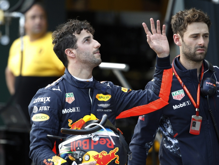 Red Bull Racing driver Daniel Ricciardo of Australia, left, waves as he walks down pit lane after crashing out of the qualifying session for the Australian Formula One Grand Prix in Melbourne, Saturday, March 25, 2017. (Brandon Malone/Pool via AP)