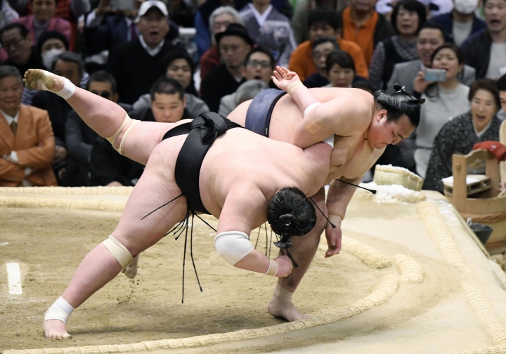 Japanese yokozuna, or grand champion, Kisenosato, top, throws Mongolian Terunofuji out of the ring during a playoff of the Spring Grand Sumo Tournament in Osaka, western Japan, Sunday, March 26, 2017. Making his debut at sumo's highest rank of grand champion, Kisenosato won the 15-day tournament in dramatic fashion on Sunday. Needing a win in regulation to force a tiebreaker, Kisenosato beat Terunofuji to give both wrestlers a record of 13-2. Kisenosato then threw down Terunofuji, who holds the sport's second-highest rank of ozeki, in the playoff to wrap up the Emperor's Cup and his second straight title. (Yohei Nishimura/Kyodo News via AP)