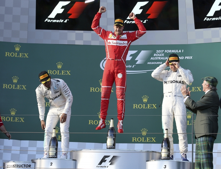 Ferrari driver Sebastian Vettel of Germany, center, jumps up as he arrives to the podium with Mercedes drivers Lewis Hamilton of Britain, left, and Valtteri Bottas of Finland as former world champion Jackie Stewart, right, applauds following the Australian Formula One Grand Prix in Melbourne, Australia, Sunday, March 26, 2017. Vettel won the race ahead of Hamilton and Bottas. (AP Photo/Rick Rycroft)