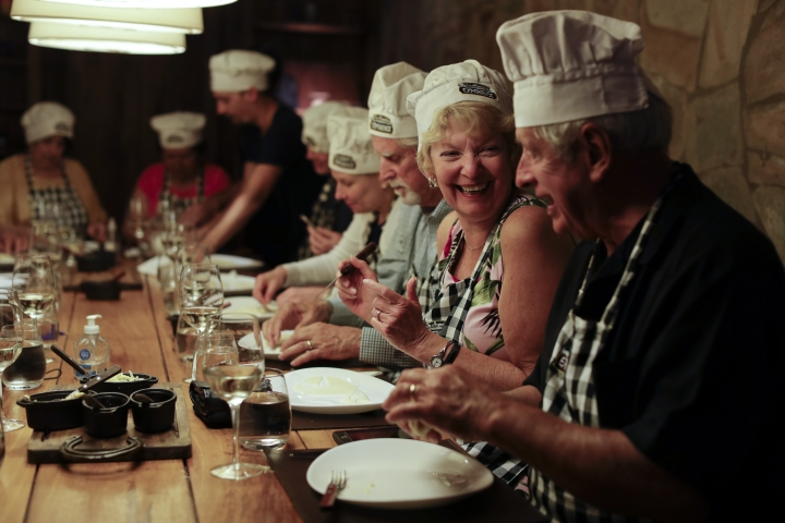 "In this March 20, 2017 photo Jane Andrews, from U.S, second left, smiles during an activity called ""The Argentine Experience"" in Buenos Aires, Argentina. Tourists participating in ""The Argentine Experience"" have the chance to learn about the local cuisine, wine and traditions during a dinner in Buenos Aires. (AP Photo/Natacha Pisarenko)"