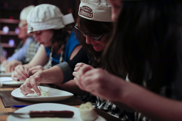 "In this March 20, 2017 photo tourist make their own ""empanada"" during an activity called ""The Argentine Experience"" in Buenos Aires, Argentina. Tourists participating in ""The Argentine Experience"" have the chance to learn about the local cuisine, wine and traditions during a dinner in Buenos Aires. (AP Photo/Natacha Pisarenko)"