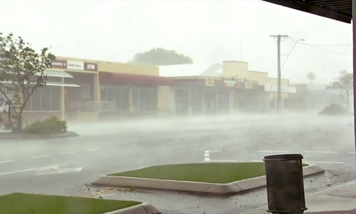 In this image made from video, wind gusts outside shops in Bowen, eastern Australia, Tuesday, March 28, 2017. A powerful cyclone lashed islands, damaged roofs and cut power on Tuesday as it edged toward Australia's tropical northeast coast, officials said.(AuBC via AP)