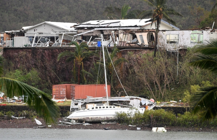 A damaged building is seen behind a boat that was pushed onto a bank due to Cyclone Debbie in the township of Airlie Beach, located south of the northern Australian city of Townsville, March 29, 2017.    AAP/Dan Peled/via REUTERS