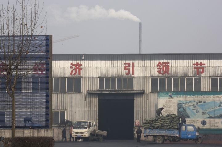 "FILE - In this Dec. 30, 2016, file photo, workers load ""clean coal"" promoted by the government at a factory in Qianan, in northern China's Hebei province. China's government said Wednesday, March 29, 2017, it will stick to its promises to curb carbon emissions after President Donald Trump eased U.S. rules on fossil fuel use that were meant to control global warming. A Chinese foreign ministry spokesman said Beijing is committed to the Paris climate agreement. (AP Photo/Ng Han Guan, File)"