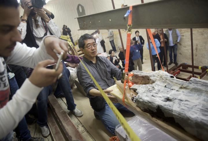 Japanese technician Kuro Koshi, from Waseda University, controls pulling operation of a giant wooden piece of Pharaoh Cheops' second solar boat below the Pyramids site in Giza, Egypt, Wednesday, March 29, 2017. Egypt is inaugurating its largest on-site antiquities laboratory, to restore the second ceremonial boat of Pharaoh Cheops, known for building the largest of Egypt's iconic pyramids. The project, funded by the Japan International Cooperation Agency and the Higashi Nippon International University, is set to complete the initial phase of repairs of the 4,500-year-old vessel by 2020. (AP Photo/Amr Nabil)