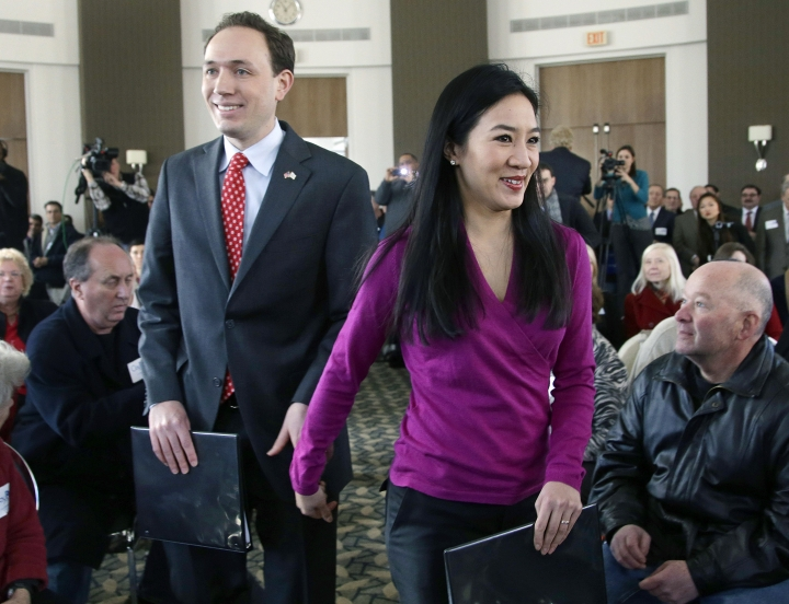 FILE - In this Jan. 28, 2014 file photo, Clay Pell, left, grandson of the late Sen. Claiborne Pell, D-RI, and his wife, two-time Olympic figure skating medalist Michelle Kwan, right, enter the Rhode Island Convention Center in Providence, R.I., to begin his campaign for governor of Rhode Island. Clay Pell said in a statement Wednesday, March 29, 2017, that the couple is getting a divorce after four years of marriage. (AP Photo/Stephan Savoia, File)
