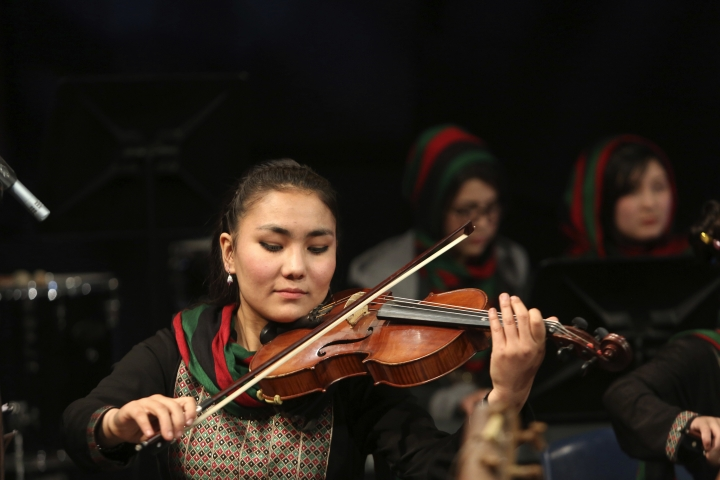 In this Wednesday, Feb. 15, 2017 photo, Zarifa Adiba, 18, an orchestra conductor in Afghanistan, plays during a concert in Kabul. Afghanistan's first all-female symphony is trying to change attitudes in a deeply conservative country where many see music as immoral, especially for women. (AP Photo/Rahmat Gul)