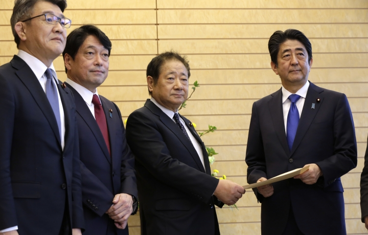 Hiroshi Imazu, second right, Chairman of Research Commission on Security of Japan's ruling Liberal Democratic Party (LDP) submits a proposal on missile defense to Japanese Prime Minister Shinzo Abe, right, flanked by former Defense Minister Itsunori Onodera, second left, head of LDP panel, at the prime minister's office in Tokyo, Thursday, March 30, 2017. Japan's ruling party has urged the government to consider arming itself with more advanced and offensive capability, such as striking enemy targets with cruise missiles, loosening Japan's self-defense-only military posture since the end of World War II. (AP Photo/Eugene Hoshiko, Pool)