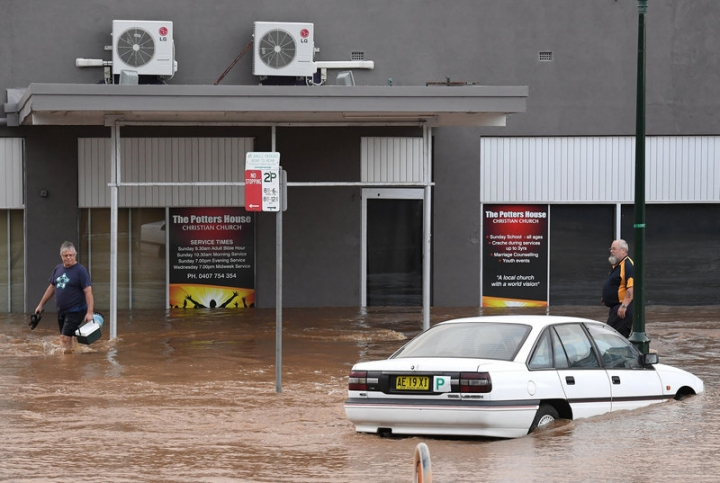 Local residents walk past a damaged car as floodwaters enter the main street of the northern New South Wales town of Lismore, Australia, March 31, 2017 after heavy rains associated with Cyclone Debbie swelled rivers to record heights across the region.      AAP/Dave Hunt/via REUTERS