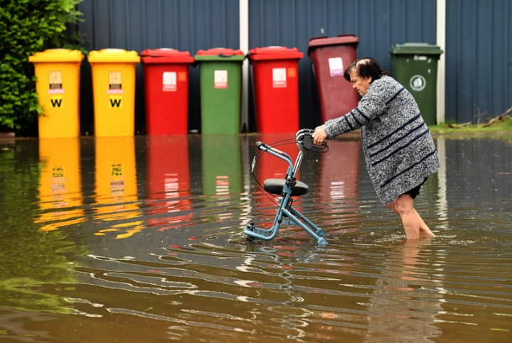 A local resident uses a support device to walk through floodwaters in the northern New South Wales town of Lismore, Australia, March 31, 2017 after heavy rains associated with Cyclone Debbie swelled rivers to record heights across the region.      AAP/Dave Hunt/via REUTERS