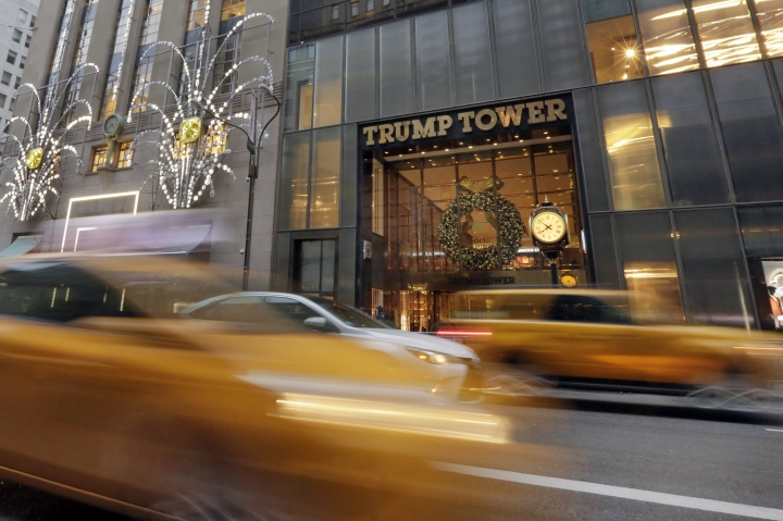 FILE - In this Nov. 29, 2016, file photo, morning traffic on Fifth Avenue passes Trump Tower, in New York. For decades, President Donald Trump's identity was interwoven with his hometown of New York City: big, brash and dedicated to making money. Manhattan was the imposing backdrop as Trump transformed himself from local real-estate developer to celebrity businessman, skyscrapers and gossip pages featured his name, and during last year's presidential campaign he'd fly thousands of miles to sleep in his own bed at Trump Tower. (AP Photo/Richard Drew, File)