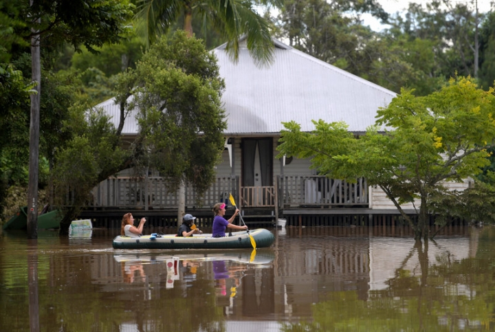 Locals float past a house in a boat on a flooded street in the northern New South Wales town of Lismore, Australia, April 1, 2017 after heavy rains associated with Cyclone Debbie swelled rivers to record heights across the region. Picture taken April 1, 2017.    AAP/Tracey Nearmy/via REUTERS