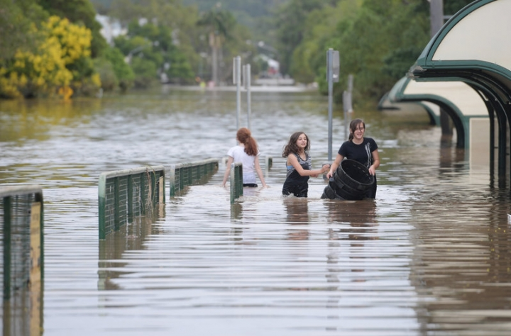 Locals walk through a flooded street in the northern New South Wales town of Lismore, Australia, April 1, 2017 after heavy rains associated with Cyclone Debbie swelled rivers to record heights across the region.   AAP/Tracey Nearmy/via REUTERS