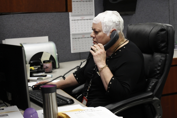 In this March 29, 2017 photo, Joyce Endresen wears an Optune therapy device for brain cancer, as she speaks on a phone at work in Aurora, Ill. She was diagnosed in December 2014 with Glioblastoma. She had two surgeries to remove the tumor as well as radiation and chemotherapy, but is now trying the new therapy that requires her to wear the electrodes on her head as much as possible. They create low intensity electric fields that disrupt cell reproduction, which makes the cells die. (AP Photo/Carrie Antlfinger)
