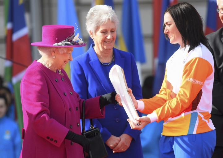 FILE - In this March 13, 2017 file photo, retired Australian cyclist Anna Mears, right, receives the Commonwealth Games relay baton from Britain's Queen Elizabeth II at the launch of the relay at Buckingham Palace in London as the XXI Commonwealth Games are being held on the Gold Coast in Australia in 2018. (Toby Melville/Pool Via AP, File)