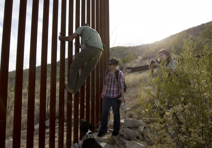 FILE - In this May 11, 2016, file photo, Tim Foley shows how to climb a section of the border wall separating Mexico and the United States near where it ends as journalists Chitose Nakagawa, right, and Marcie Mieko Kagawa look on in Sasabe, Ariz. Foley, a former construction foreman, founded Arizona Border Recon, a group of armed volunteers who dedicate themselves to border surveillance. With bids due Tuesday, April 4, 2017, on the first border wall design contracts, companies are preparing for the worst if they get the potentially lucrative but controversial job. (AP Photo/Gregory Bull, File)