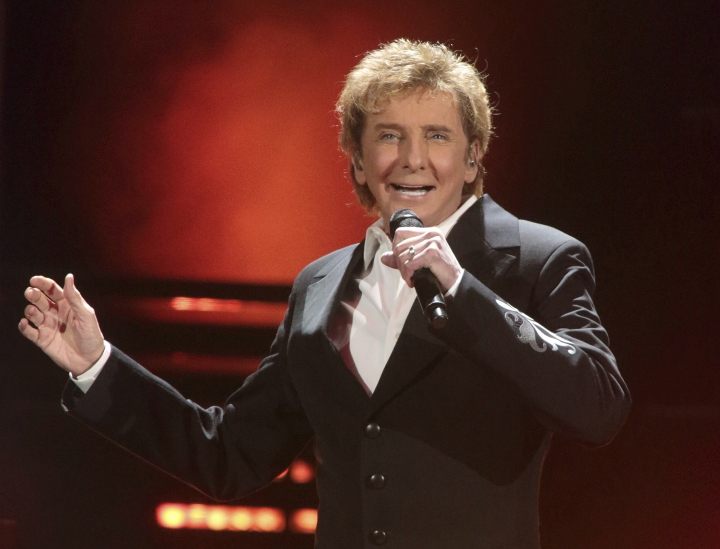"""FILE - In this March 17, 2016 file photo, Barry Manilow performs in concert during his """"One Last Time! Tour 2016"""" in Hershey, Pa. Manilow tells People magazine that he hid being gay for decades because he thought he would be """"disappointing fans if they knew."""" The 73-year-old music legend married his longtime manager, Gary Kief, in a 2014 ceremony at their home in Palm Springs, Calif. Manilow tells the magazine's April 17 issue that keeping their romance out of the media was stressful. (Photo by Owen Sweeney/Invision/AP, File)"""